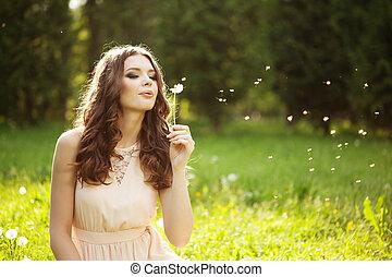 Beautiful woman blowing a dandelion - Beautiful young woman...