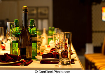 Drinks on a formal dinner table with bottles of mineral...
