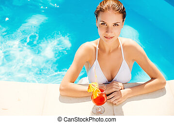 Enjoying summer at the pool. Top view of beautiful young woman in white bikini holding cocktail and smiling while standing at the pool