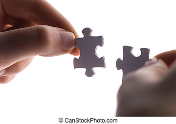 close up of two hands trying to connect puzzle pieces. Hands with two puzzles Isolated on white background