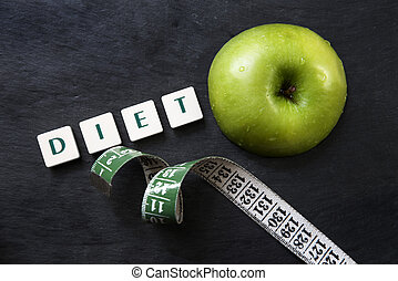 Dieting - Green apple with measuring tape and scrabble...