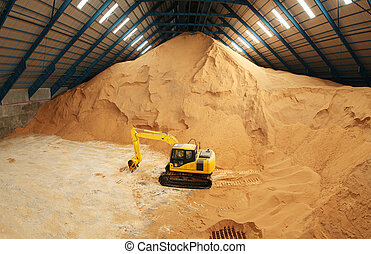 Excavator in a raw sugar storage