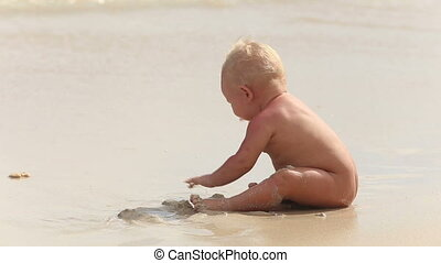 baby crawling on the sand and sees it then smiles