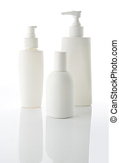 lotion bottles - Three white cosmetic bottles stand on a...