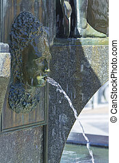 Old bronze fountain with the face of a woman