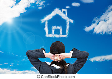 Businesswoman Looking At House Shaped Cloud