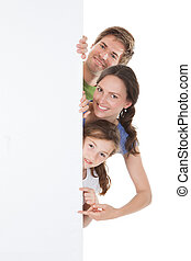 Happy Family Peeking From Blank Billboard - Portrait of...