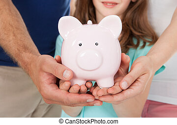 Family Holding Piggy Bank - Midsection of family holding...