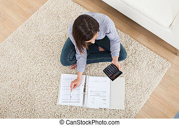 Woman Calculating Home Finances On Rug - High angle view of...