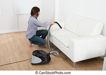Young Woman Vacuuming Sofa At Home - Full length side view...