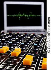 Music Mixer - Analog studio music mixer closeup with laptop...