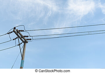 transformers of an electrical post with power-lines against...