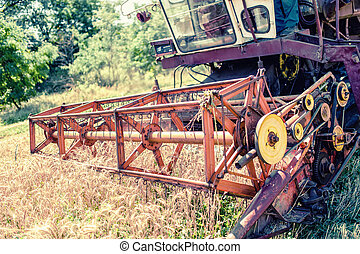 Close-up of harvesting combine in grain and wheat crops....