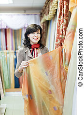 woman  chooses draperies at shop