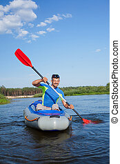 Young man kayaking - Summer vacation - Young man kayaking on...