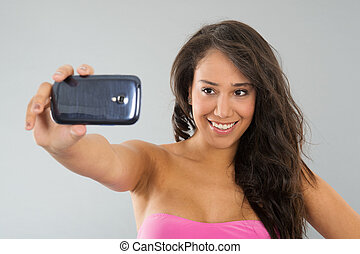 Black woman taking selfie - Young attractive black woman is...