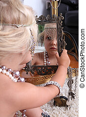 little girl plays with jewelry and look in mirror