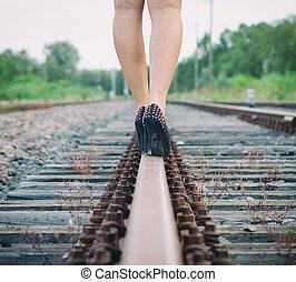 Woman legs walking on railway.