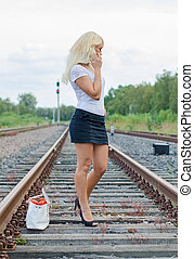 Woman missed the train. Calling someone on the phone.