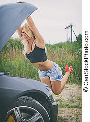 Sexy young blond woman inspecting car engine