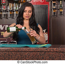 young woman pouring drink in pub - attractive young barmaid...