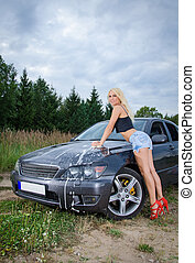 Sexy young blonde woman washes sport car