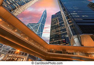 Hong Kong streetscape at night. Pedestrian passage and tall...