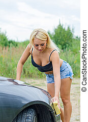 Sexy woman washing car with sponge