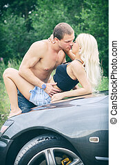 Sensual couple making love on the cars hood