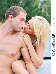 Sexy young couple kissing on the cars hood