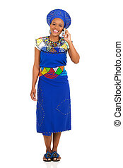 african zulu woman talking on mobile phone - full length...