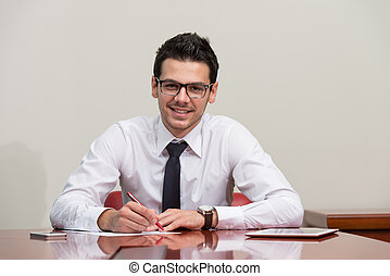 Businessman Sitting At Office Desk Signing A Contract -...