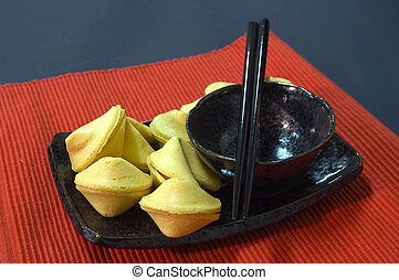 Fortune cookies on a plate with a black bowl and chopsticks...