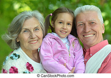 Grandparents with granddaughter - Cute grandparents smiling...