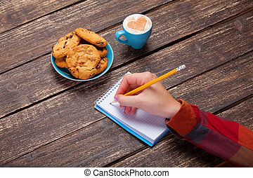 Female hand writing something in note near cookie and cup of...