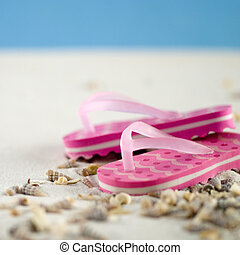Flip Flops - pair of pink flip flops in the sand