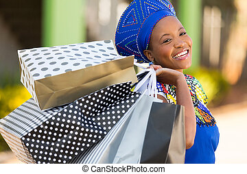 african shopper carrying shopping bags in mall - happy...