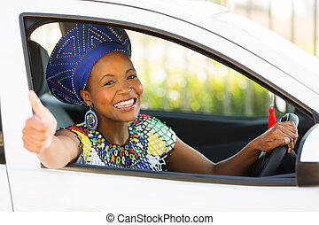 south african woman giving thumb up inside her car