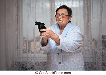 Senior woman with a gun - Scared senior woman aiming a gun...