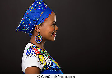 young african zulu woman on black background - side view of...