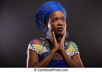 thoughtful african zulu woman looking up isolated on black...