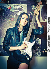Brunette in leather with guitar - Beautiful brunette with...