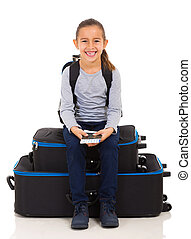 little girl sitting on luggage bags