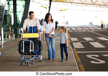 young family at airport with a trolley full of luggage -...