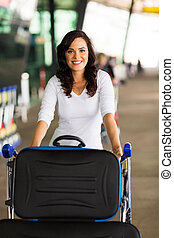 woman at airport with a trolley full of luggage
