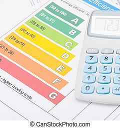 Calculator over energy efficiency chart - studio shot - 1 to...