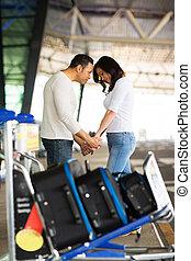 man comforting his girlfriend at airport