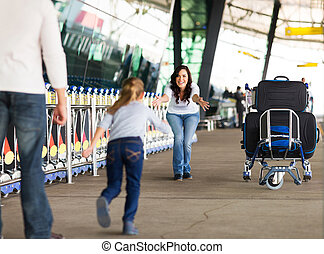 young girl running to her mother at airport after a long...