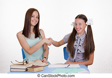 Teacher and student happily shake hands with each other -...