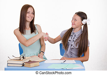 Teacher and student shake hands with each other - The...